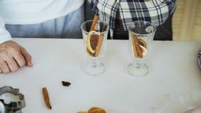 Le plan rapproché des couples remet mélanger les condiments dans un verre pour le vin chaud dans la cuisine à la maison banque de vidéos