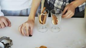 Le plan rapproché des couples remet mélanger les condiments dans un verre pour le vin chaud dans la cuisine à la maison Photo libre de droits