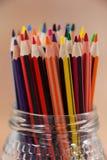 Le plan rapproché des crayons colorés a maintenu dans un pot en verre Photo stock