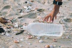 Le plan rapproché des enfants de bras prennent les bouteilles en plastique photo stock