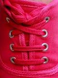 Le plan rapproché des espadrilles roses vibrantes occasionnelles chausse des bottes sur les pieds femelles Images libres de droits