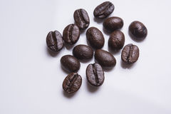 Le plan rapproché des grains de café rôtis amassent d'isolement sur le blanc studio photos stock