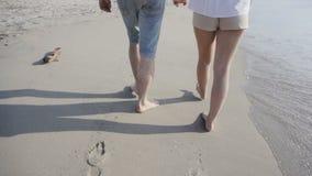 Le plan rapproché des jambes de pieds nus marchent le long de la plage banque de vidéos