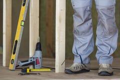 Le plan rapproché des jambes du ` s de travailleur et des outils professionnels de bâtiment au cadre en bois pour le futur mur da photographie stock libre de droits