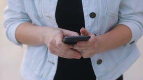 Le plan rapproché des jeunes offrent la fille dans le manteau blanc de jeans et le T-shirt noir communiquant avec un mouvement le banque de vidéos
