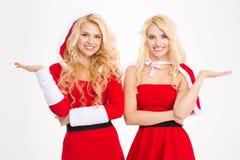 Le plan rapproché des jumeaux dans Santa costume tenir le copyspace sur des paumes Photographie stock libre de droits