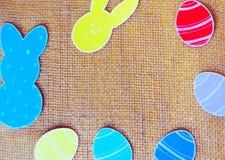 Le plan rapproché des lapins et du papier de papier colorés eggs des cadres de silhouette sur le fond de toile Image stock