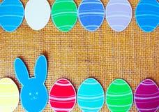 Le plan rapproché des lapins et du papier de papier colorés eggs des cadres de silhouette sur le fond de toile Photos stock
