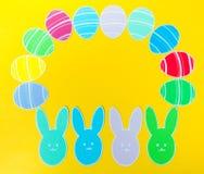 Le plan rapproché des lapins et du papier de papier colorés eggs des cadres de silhouette sur le fond de toile Photographie stock