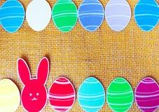 Le plan rapproché des lapins et du papier de papier colorés eggs des cadres de silhouette sur le fond de toile Image libre de droits