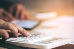 Le plan rapproché des mains d'homme d'affaires dirigeant la calculatrice dans écoutent Images stock