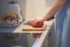 Le plan rapproché des mains de femme a coupé le poivron rouge dans la cuisine Photos libres de droits