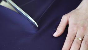 Le plan rapproché des mains de jeune femme a coupé le tissu bleu avec des ciseaux selon le modèle banque de vidéos