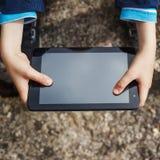 Le plan rapproché des mains de l'enfant se ferment vers le haut de tenir le comprimé numérique Photos stock