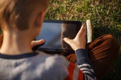 Le plan rapproché des mains de l'enfant se ferment vers le haut de tenir le comprimé numérique pour le pla Photo stock