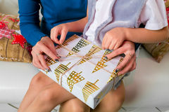 Le plan rapproché des mains de mère et de fils ouvrent le boîte-cadeau de Noël Image stock
