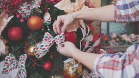Le plan rapproché des mains femelles décorent l'arbre de Noël Image stock
