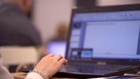 Le plan rapproché des mains femelles introduisant le message textuel sur l'ordinateur portable, jeune étudiant s'asseyant lors d' banque de vidéos