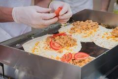 Le plan rapproché des mains font cuire faire les fajitas ou les fajitos frais sains avec du fromage, boeuf, tomates Très chaud se illustration libre de droits