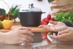 Le plan rapproché des mains humaines sont gesticulent au-dessus d'une table dans la cuisine Femmes choisissant le menu ou faisant Images libres de droits