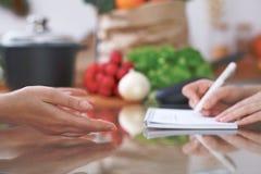 Le plan rapproché des mains humaines sont gesticulent au-dessus d'une table dans la cuisine Femmes choisissant le menu ou faisant Photo stock