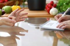 Le plan rapproché des mains humaines sont gesticulent au-dessus d'une table dans la cuisine Femmes choisissant le menu ou faisant Photos stock