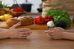 Le plan rapproché des mains humaines sont gesticulent au-dessus d'une table dans la cuisine Femmes choisissant le menu ou faisant Photographie stock