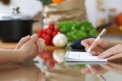 Le plan rapproché des mains humaines sont gesticulent au-dessus d'une table dans la cuisine Femmes choisissant le menu ou faisant Images stock