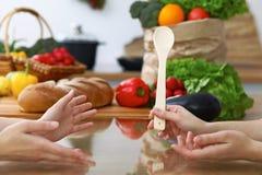 Le plan rapproché des mains humaines sont gesticulent au-dessus d'une table dans la cuisine Femmes choisissant le menu ou faisant Photo libre de droits