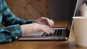 Le plan rapproché des mains masculines utilisant l'ordinateur portable au bureau, le ` s d'homme remet la dactylographie sur le c banque de vidéos