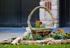 Le plan rapproché des pensées s'élevant derrière le paysage bascule près d'une statue de lapin et de panier devant une maison - f images stock