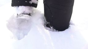 Le plan rapproché des pieds du ` s de l'homme marchant sur les montagnes rejette des pieds dans la neige Pelliculage au ralenti banque de vidéos