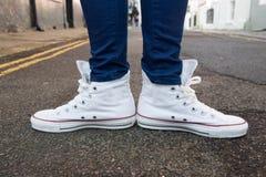 Le plan rapproché des pieds femelles dans des espadrilles à la mode se tiennent sur le trottoir Photographie stock