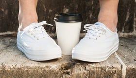Le plan rapproché des pieds femelles se tenant sur des escaliers s'approchent de la tasse de café Photo libre de droits