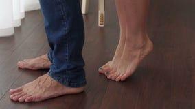 Le plan rapproché des pieds nus d'un couple affectueux, la fille se tient sur ses orteils clips vidéos