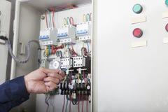 Le plan rapproché des travailleurs remettent vérifier les contrôles et le câblage dans une usine à gaz, Pékin, Chine Images libres de droits