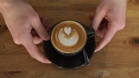 Le plan rapproché du barman masculin met une tasse de latte avec un coeur sur la mousse sur la table banque de vidéos
