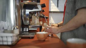 Le plan rapproché du barman professionnel verse le café de la machine de café Art Maîtrise dans la gestion de l'équipement de caf banque de vidéos