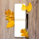 Le plan rapproché du carnet et du stylo, décoré du jaune d'automne part et s'embranche Vue supérieure, configuration plate Photo stock
