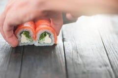 Le plan rapproché du chef remet le roulement vers le haut des sushi photos stock