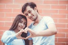 Le plan rapproché du coeur de fabrication asiatique de jeune homme et de femme forment avec la main Images libres de droits
