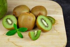 Le plan rapproché du kiwi vert frais se trouvant sur une table en bois légère, tranche de kiwi, a empilé le kiwi sur une table en Image stock