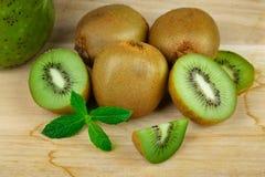 Le plan rapproché du kiwi vert frais se trouvant sur une table en bois légère, tranche de kiwi, a empilé le kiwi sur une table en Images stock