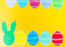 Le plan rapproché du lapin et du papier de papier colorés eggs des cadres de silhouette sur le fond de toile Photographie stock