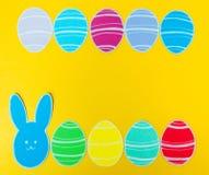 Le plan rapproché du lapin et du papier de papier colorés eggs des cadres de silhouette sur le fond de toile Photographie stock libre de droits