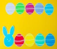 Le plan rapproché du lapin et du papier de papier colorés eggs des cadres de silhouette sur le fond de toile Photos stock