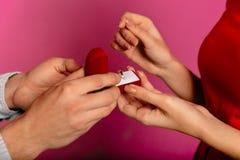 Le plan rapproché du mâle remet le boîte-cadeau d'ouverture avec la bague de fiançailles à son amie Photo libre de droits