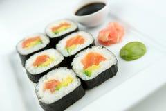 Le plan rapproché du maki saumoné frais de sushi roule avec du gingembre, le wasabi et la sauce de soja photo stock