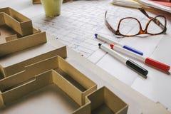 Le plan rapproché du modèle de bâtiment et les outils de rédaction sur une construction prévoient. Photographie stock libre de droits