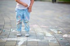 Le plan rapproché du pantalon du ` s de petit garçon a souillé avec des craies Images stock